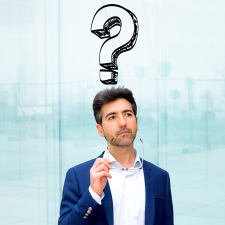 Portrait view of an attractive stressed business man with question mark icons surrounding his head - Problem concept Stock Photo