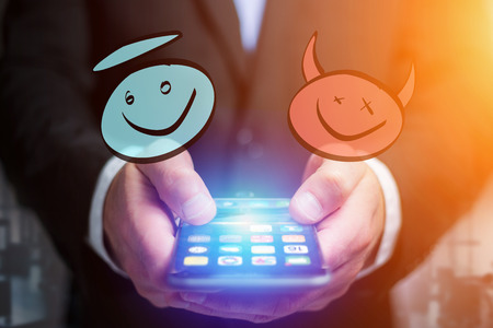 View of Hand drawn angel and demon icon going out a smartphone interface of a businessman at the office - Business concept Stock Photo