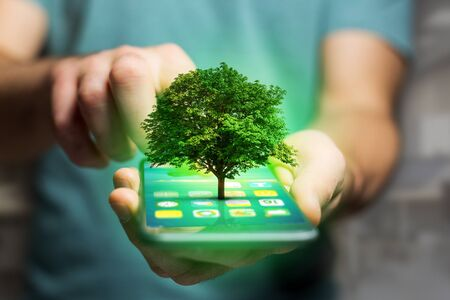 View of a Green tree going out of a smartphone - Ecology concept