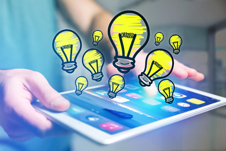 View of Hand drawn bulb lamp icon going out a tablet interface of a businessman at the office - ideas concept Stock Photo