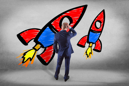 colorfull: View of a Businessman in front of a wall thinking about a colorfull start up rocket - business concept