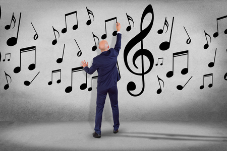 View of a Businessman in front of a wall writing music notes - Art concept