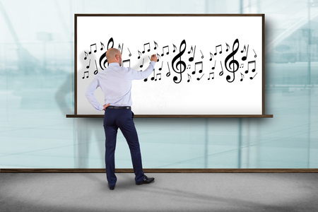 partition musique: View of a Businessman in front of a wall writing music notes - Art concept