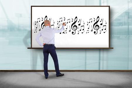 Vue d'un homme d'affaires devant un mur en train d'écrire des notes de musique - Concept d'art Banque d'images