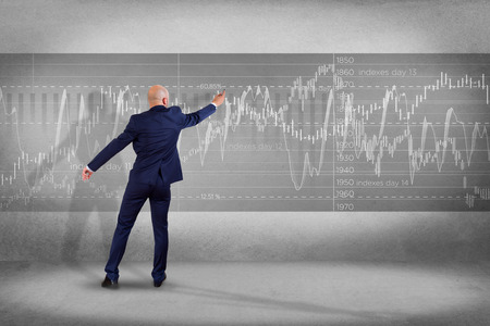 rate: View of a Man in front of a wall writing on a stock exchange interface - tradex concept