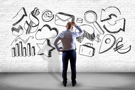 View of a Businessman in front of a wall thinking about a hand drawn business interface - business concept