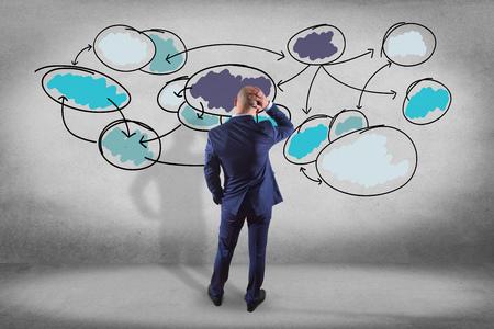 Ansicht eines Geschäftsmannes vor einer Wand, die eine Geschäftsdiagrammorganisation betrachtet - Geschäftskonzept Standard-Bild