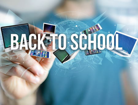 View of a Back to school title surounded by device like smartphone, tablet or laptop - Internet and communication concept Archivio Fotografico