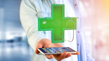 View of a Businessman using a smartphone with a Lighting pharmacy cross and a stethoscope - 3d render  Stock Photo