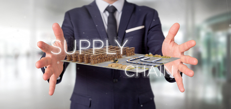 View of a Businessman holding a Supply Chain title with a warehouse on background 3d rendering