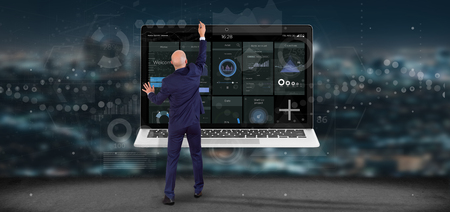 View of Businessman in front of a wall with Laptop with business user interface data on the screen