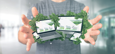 View of a Businessman holding connected devices surrounding by leaves 3d rendering Foto de archivo