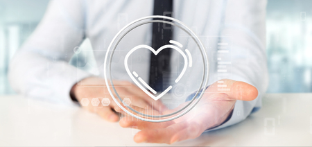 View of a Businessman holding a heart icon surrounded by data