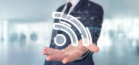 View of a Businessman holding a wifi icon with data all around