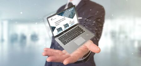 View of a Businessman holding a Laptop with business website template on the screen isolated on a background Banco de Imagens - 129469420
