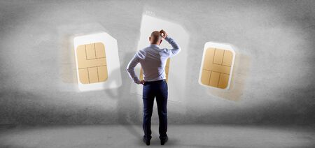 View of a Businessman holding Different size of a smartphone sim card 3d rendering 스톡 콘텐츠 - 132114007