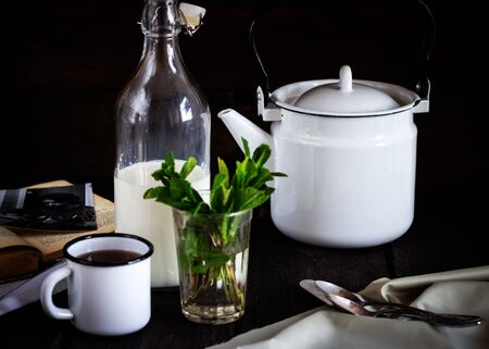 cosiness: A teapot, cup and a bottle of milk on a wooden table