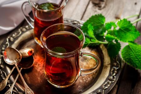 comida arabe: té con menta en el estilo árabe en mesa de madera Foto de archivo