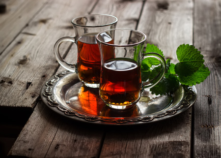 arabic food: tea with mint in the Arab style on wooden table Stock Photo