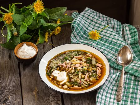okroshka: Traditional Russian kvass soup with vegetables  okroshka in a bowl on wooden table. Stock Photo