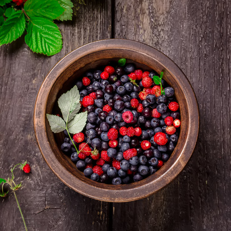 summer fruit: Bowl with wild berries on dark wooden background. Style rustic. Square. Stock Photo