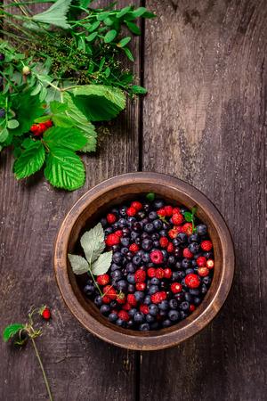 Ciotola di legno con frutti di bosco selvatici fiori di bosco e tovagliolo sul tavolo di legno scuro. Stile rustico.