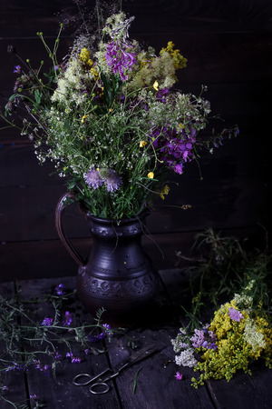 medow: Jug with flowers from a medow on dark wooden table. Style rustic, selective focus.