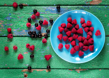 cracky: Summer berries on blue plate on old rustic painted cracky green (turqouise) wooden background. Selective focus.