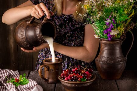 raspberry dress: The girl pouring milk from a jug into a cup and a bowl with berries on a wooden table. Jug with flowers. Dark background. Selective focus. Stock Photo