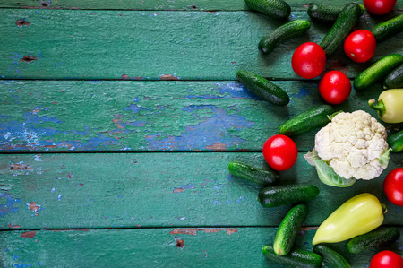craked: Summer vegetables: cucumbers, tomatoes,pepper on old green wooden background. Stock Photo