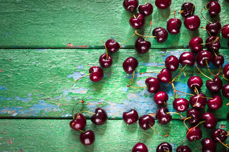cracky: Cherry on old rustic painted cracky green (turqouise) wooden background.