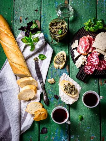 antipasti: Antipasti on chopping board, knife,baquette,basil,two glasses of wine. Old green wooden background. Stock Photo