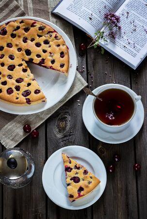 cherry pie: Cherry pie, tea and book on grey wooden background. Selective focus.