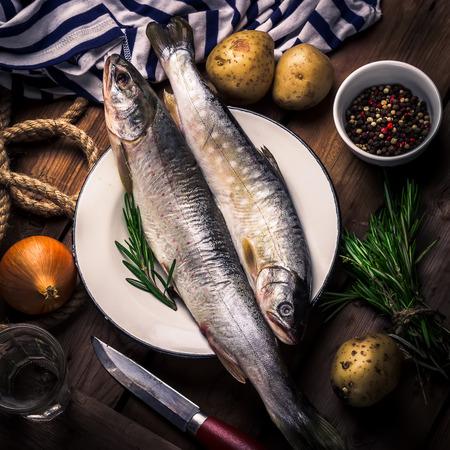 burbot: pescado de r�o en bruto con patatas, cebolla, especias y hierbas en una mesa de madera. estilo r�stico, enfoque selectivo. Foto de archivo