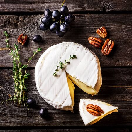 overhead view: Cheese, herbs, nuts and grape on dark wooden table. Overhead view. Style rustic.