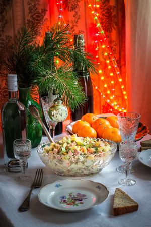soviet union: The table laid by new year in soviet union style. Serving of Russian Salad Olivier, tangerines  and champagne.