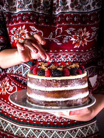 layer style: Layer cake on white plate in female hands. Style rustic. Stock Photo