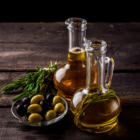 olive green: Two  bottles of olive oil, olive in a bowl and herbs on a wooden table. Selective focus. Stock Photo