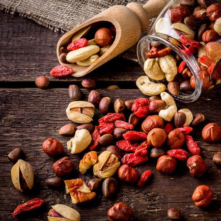 frutos secos: Scatterede tuercas y pala. fondo de madera, enfoque selectivo.
