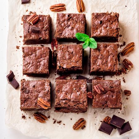 Brownie-stukken met noten op het witte papier versierd met muntbladeren. Selectieve focus. Stockfoto