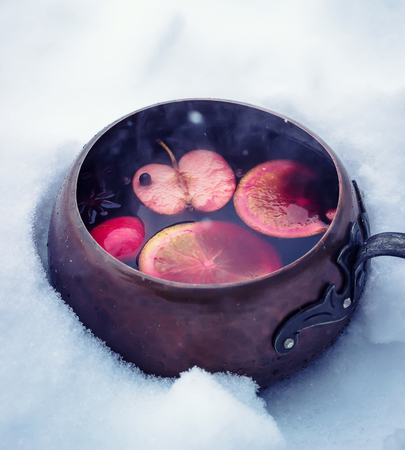 cupper: Vintage copper ladle with hot mulled wine on snow. winter. Outdoor.Selective focus.