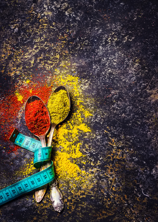 centimeter: Spices in spoons and centimeter on dark stone background.