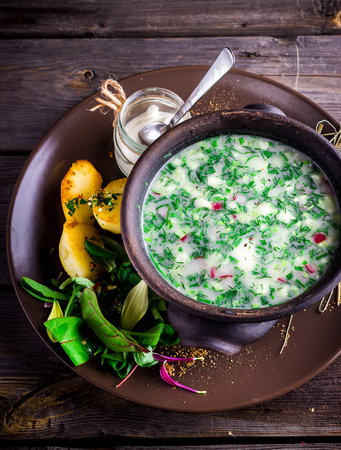 okroshka: Traditional Russian kvass soup with vegetables - okroshka in a bowl on wooden table. Style rustic.