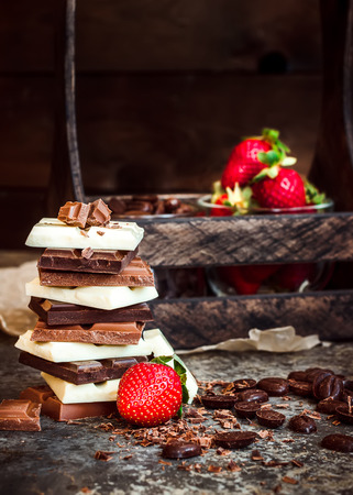 Chocolate  Chocolate bar  chocolate backgroundchocolate tower and strawberry.  Dark  background. Selective focus. Stock Photo