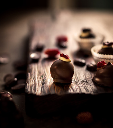 cafe bombon: Chocolate sweets with dried berries and chocolate beans on dark background. Selective focus.