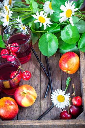Cherry lemonade with summer fruits and flowers in wooden box. Stock Photo