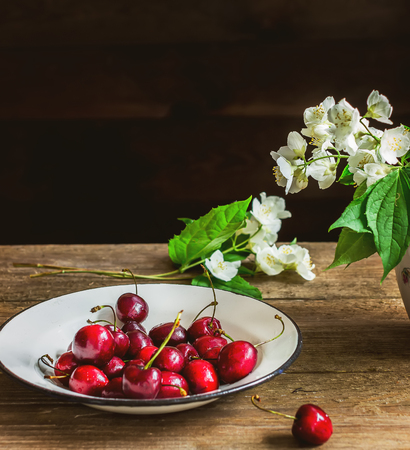 rust red: Sweet cherry in white bowl on wooden table. Style rustic. Selective focus.