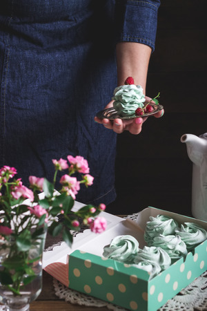 raspberry dress: Meringue dessert decorated with raspberry in female hand, other meringues in box on wooden table. Flowers in glass. Selective focus.