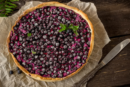 bilberry: Homemade pie with bilberry decorated by bilberry leaves on dark wooden table.Style rustic. Selective focus. Stock Photo