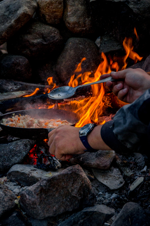 turistic: Cooking over a campfire by man.  Turistic scene. Selective focus.
